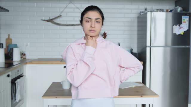 eine junge inderin steht in einem hellen raum und schaut nachdenklich in die kamera - weibliche führungskraft stock-videos und b-roll-filmmaterial