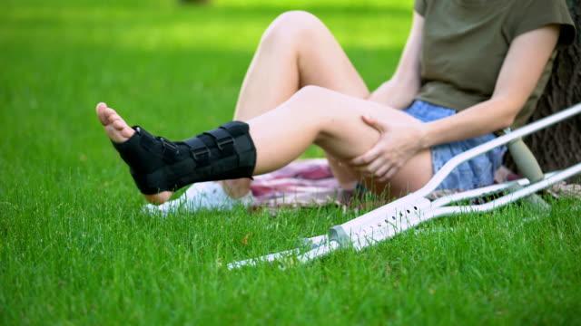 vídeos de stock, filmes e b-roll de fêmea ferida nova com a cinta e as muletas de apoio do tornozelo que sentam a grama do parque - ortopedia