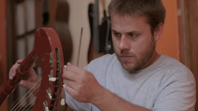 Young instrument maker fastening the pegs of a harp using a screwdriver at studio