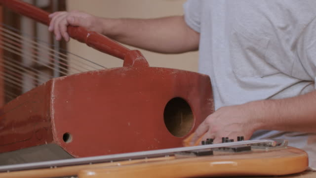 Young instrument maker removing dust of harp with a cloth on the workbench of studio