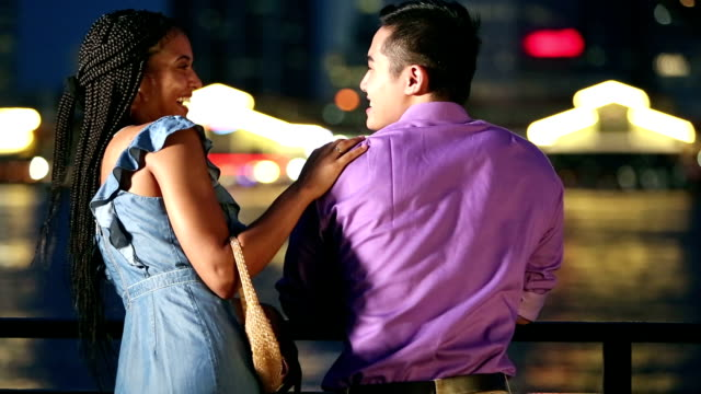 Young interracial couple conversing on city waterfront A young interracial couple standing on a city waterfront conversing. They are leaning against the railing, water and buildings out of focus in the background. It is nighttime. date night romance stock videos & royalty-free footage