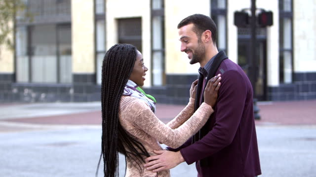 Young interracial couple meeting in city A young interracial couple meeting in the city. The man is waiting with arms crossed when his African-American girlfriend walks up. They embrace, smiling at each other and talk. boyfriend stock videos & royalty-free footage