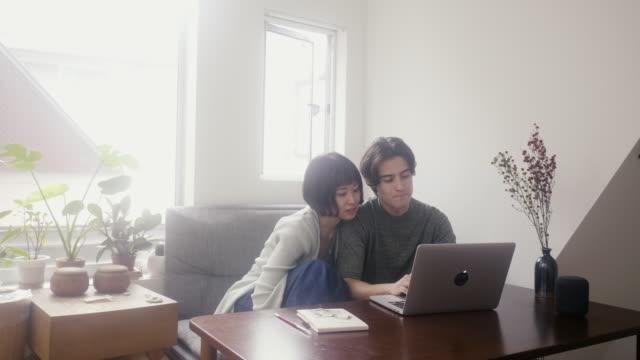 vídeos de stock e filmes b-roll de young interracial couple shopping online - casal jovem