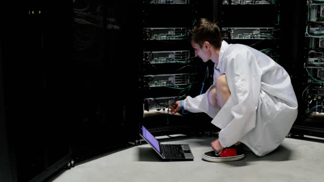 Young IT Technician Using Laptop for Work in Server Room Young IT Technician Using Laptop for Work in Server Room. supercomputer stock videos & royalty-free footage