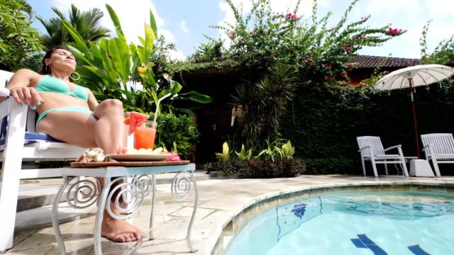 太陽とバリ島でのプライベートヴィラでプールで健康的なジュースを楽しむ若いイタリア人の女の子 - ヴィラ点の映像素材/bロール