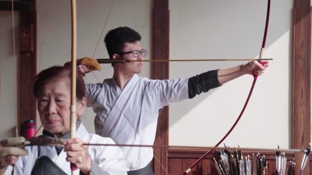 弓道の伝統的なスポーツを練習する若い日本の射手 - 武道点の映像素材/bロール