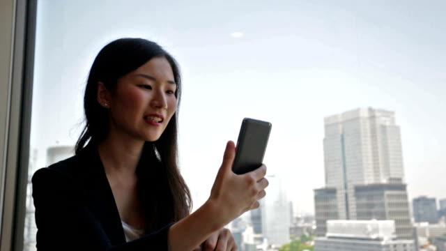 若いビジネスウーマンのビデオまでお電話ください。 - テレビ会議 日本人点の映像素材/bロール