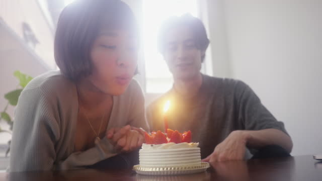 Young japanese female blowing a candle on strawberry sponge cake on Christmas