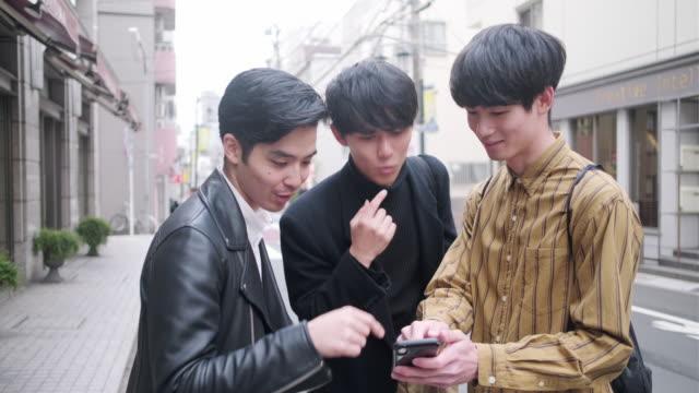 unga japanska manliga vänner kontroll karta online i urban tokyo - japan bildbanksvideor och videomaterial från bakom kulisserna