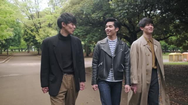 young japanese male friends walking in tokyo park - fianco a fianco video stock e b–roll