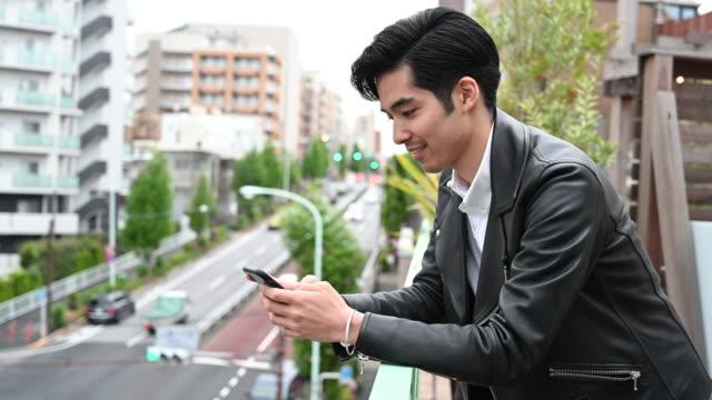 スマートフォンを使った日本の若者が見上げる - 上半身点の映像素材/bロール