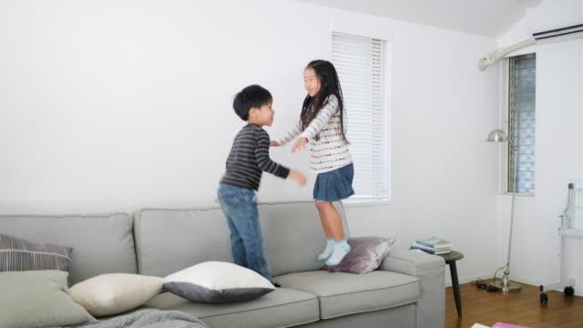 若い日本の兄弟がソファでジャンプして遊ぶ - 兄弟姉妹点の映像素材/bロール