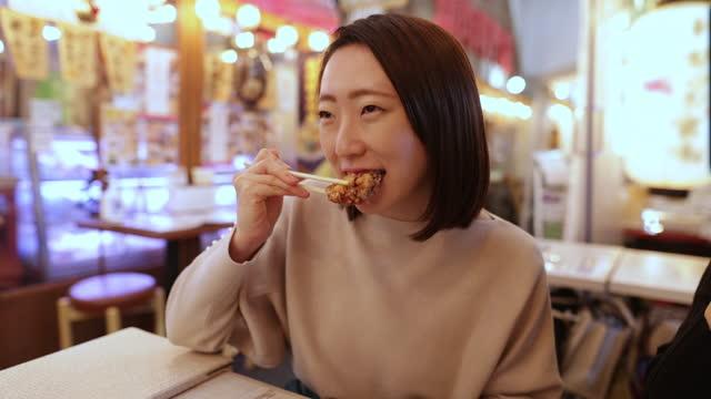 giovane donna giapponese che mangia pollo fritto nel bar izakaya - antipasto video stock e b–roll