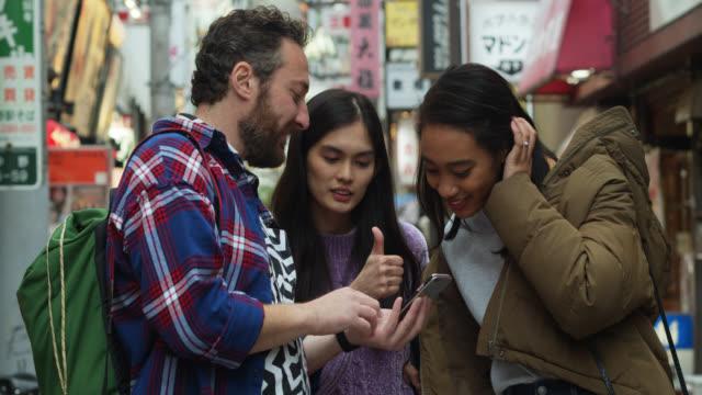 vídeos y material grabado en eventos de stock de jóvenes mujeres japonesas dirigiendo turista en tokio - turista