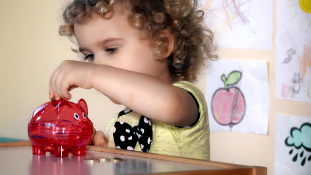 young kid putting euro coins into a piggybank sitting near table video