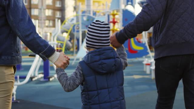 bambini che camminano verso il parco giochi con i genitori - parco giochi video stock e b–roll