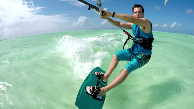 CLOSE UP: Young kiter on summer vacation kiteboarding on perfect turquoise sea video