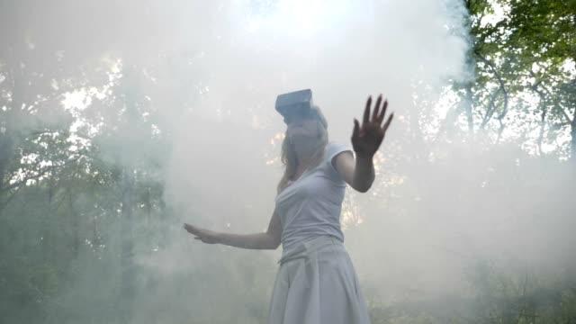 stockvideo's en b-roll-footage met jonge dame ontdekt dat een hele nieuwe wereld van virtuele werkelijkheid met behulp van vr bril buiten in de natuur - new world