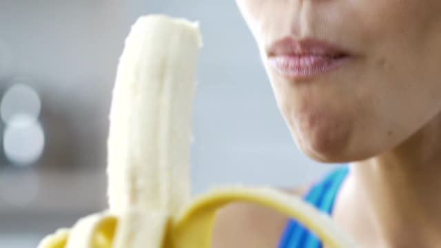 Young lady eating banana and smiling, quick and healthy snack on break, calories video