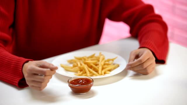 giovane donna che mangia patate fritte con salsa di pomodoro, pasto dannoso, calorie - immergere video stock e b–roll