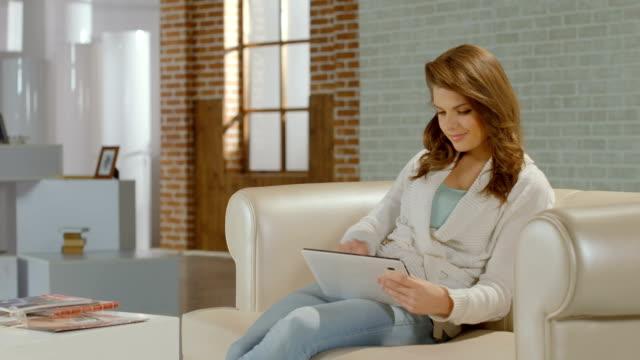 молодая леди, наслаждаясь работу в новый планшетный пк приложение, улыбается - google стоковые видео и кадры b-roll