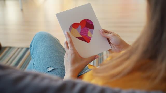 バレンタインカードを持っている若い女性は、私はあなたが家でソファに座っているのが大好きだと言って - グリーティングカード点の映像素材/bロール