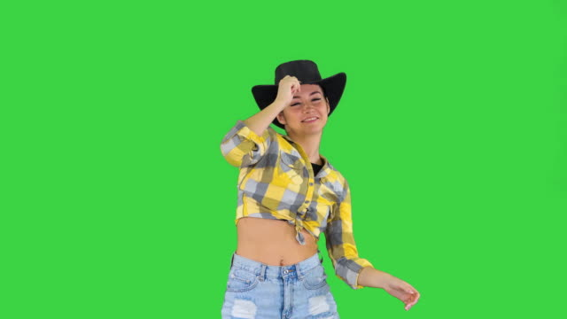 Young lady in a cowboy hat dancing on a Green Screen, Chroma Key