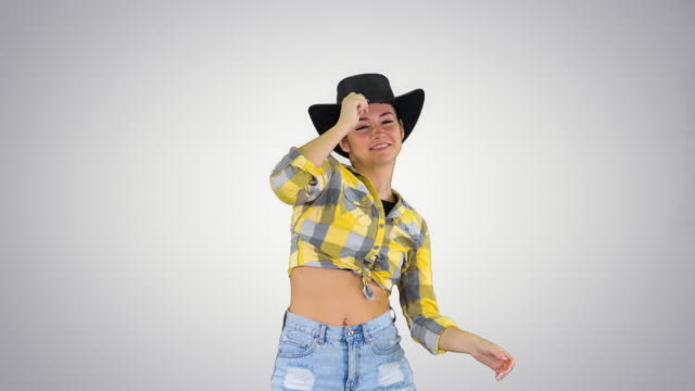 Young lady in a cowboy hat dancing on gradient background