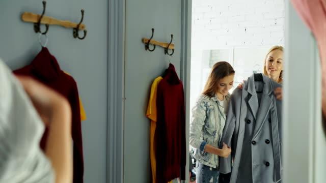 vídeos de stock, filmes e b-roll de jovem senhora em roupas casuais é tentar casaco na sala de montagem e pedir aconselhamento ao seu amigo. menina está chegando perto, verificação do vestuário e aprová-lo com um sorriso. - boutique