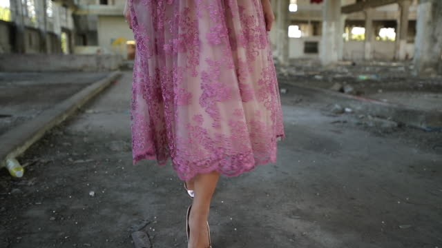 Young lady in pink dress in abandoned warehouse video