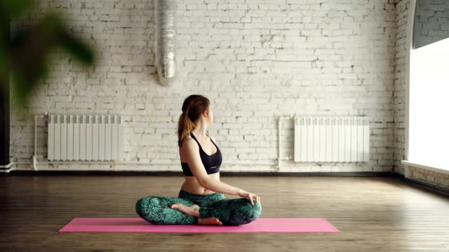 young lady in trendy sports clothing is doing body twists sitting in lotus position on mat inside yoga studio. relaxing personal practice concept. - skręcony filmów i materiałów b-roll
