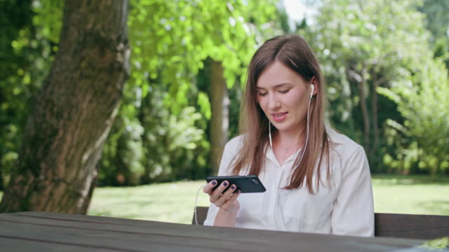 young lady listening to music in the park - tavolo legno video stock e b–roll