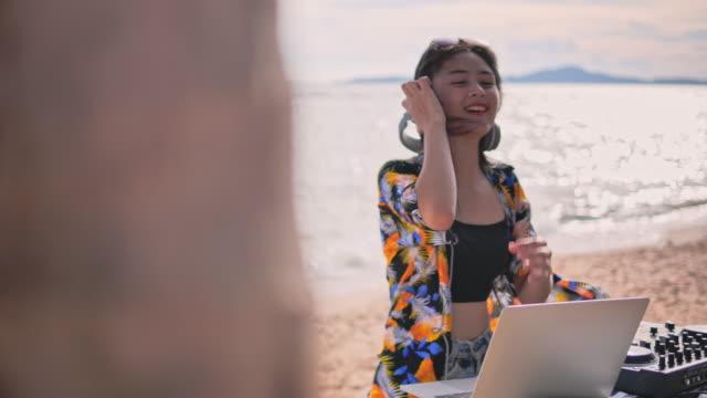 vídeos de stock, filmes e b-roll de música eletrônica da mistura da senhora nova na praia - dj