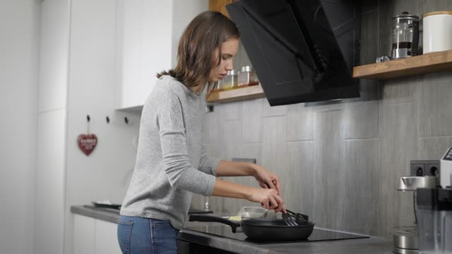 Young lady preparing food in kitchen Side view attractive woman near frying pan on fryer in modern kitchen frying pan stock videos & royalty-free footage