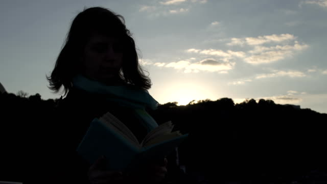 Young lady reads the book during the sunset video