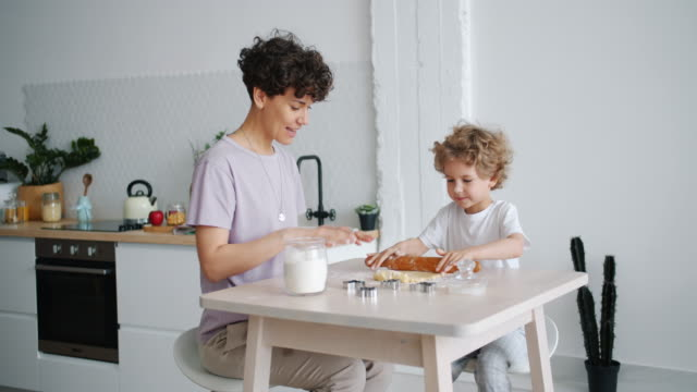Young lady teaching small boy to roll dough cooking pastry at home in kitchen