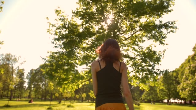 young lady turning to a camera in park. sunset or sunrise - woman portrait forest video stock e b–roll