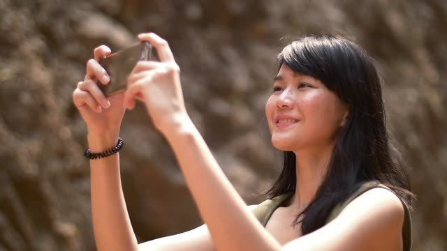 young lady use mobile phone taking photo while travelling video