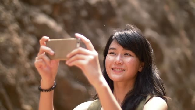 young lady use mobile phone taking photo while travelling with happy face video