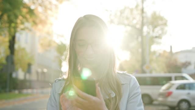 eine junge dame mit einem smartphone auf der straße - online dating stock-videos und b-roll-filmmaterial