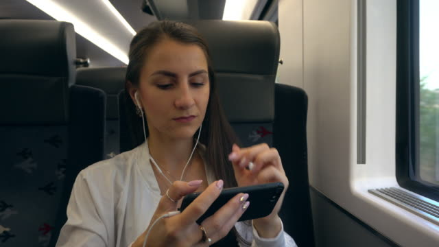 a young lady using a smartphone in the train - woman chat video mobile phone video stock e b–roll