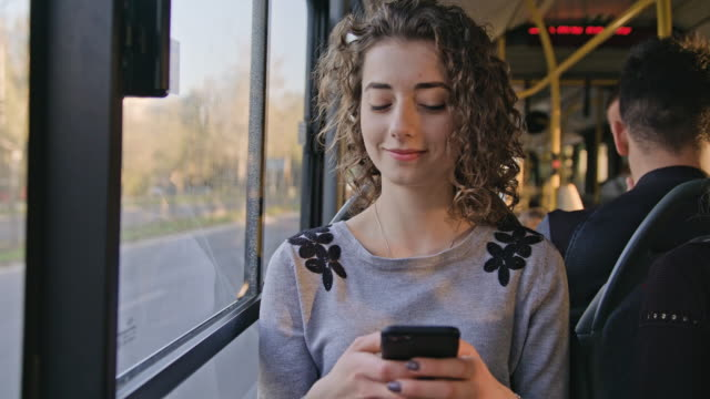 vídeos y material grabado en eventos de stock de una señora joven con un smartphone en el bus - autobús