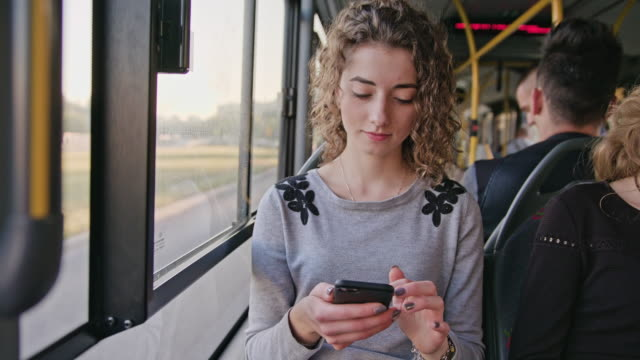a young lady using a smartphone on the bus - bus stock videos and b-roll footage