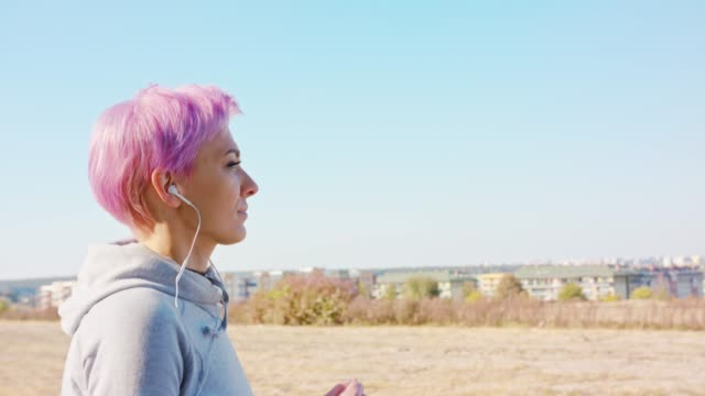 young lady with pink hair jogging in the suburbs - браслет стоковые видео и кадры b-roll