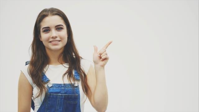 思慮深い顔をした若い女性は、左手の指でいらいらさせ、それに満足感を示している。 - 指差す 女性点の映像素材/bロール