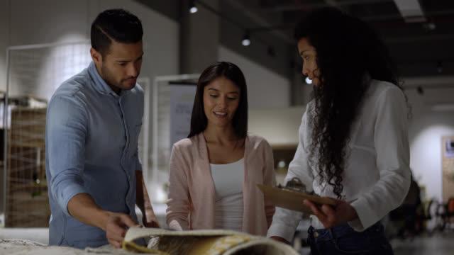 giovane coppia latinoamericana che fa shopping per tappeti in un negozio di mobili con l'aiuto di una commessa - moquette video stock e b–roll