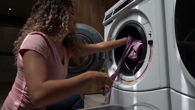 Jeune clientèle latino-américaine à une laverie automatique, chargement de la machine à laver en souriant - Vidéo