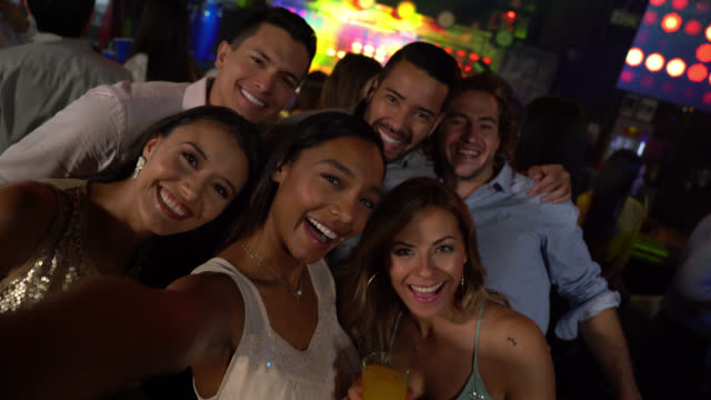 Young latin american friends clubbing and drinking taking a selfie looking at camera smiling video