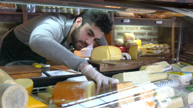 Young latin american man arranging the cheese refrigerator display at a delicatessen Young latin american man arranging the cheese refrigerator display at a delicatessen - Small business concepts homegrown produce stock videos & royalty-free footage