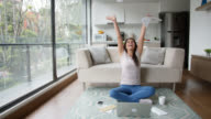 istock Young latin american woman celebrating something while working on laptop sitting on floor at home 1210447362